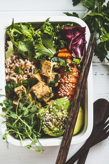 Boîte à lunch avec des aliments végétaliens sains. boîte à bento avec riz, patate douce, tofu et légumes. Photo Premium
