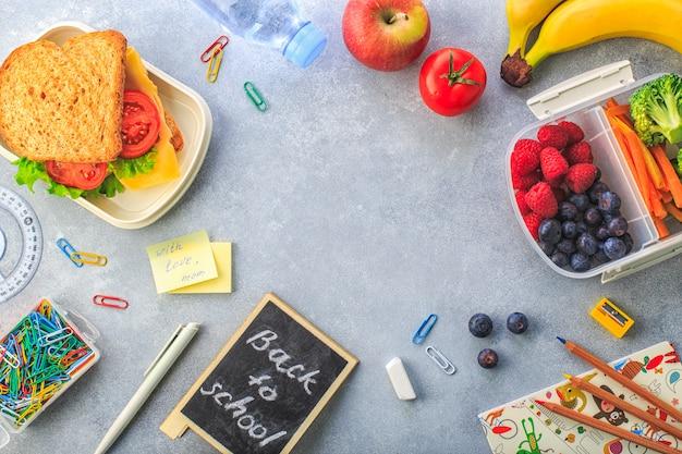 Boîte à lunch avec une bouteille de brocoli, carottes et brocoli, baies d'eau sur la vue de dessus gris Photo Premium