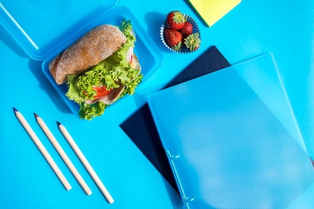 Boîte à lunch avec des dossiers et des crayons Photo gratuit