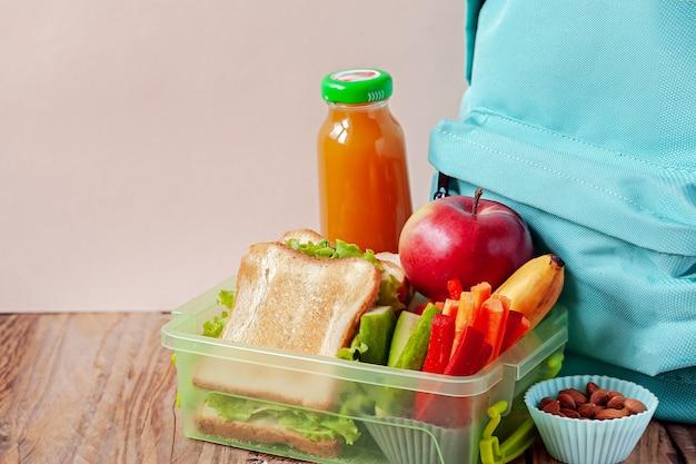 Boîte à lunch avec nourriture appétissante et sac à dos sur une table en bois. Photo Premium
