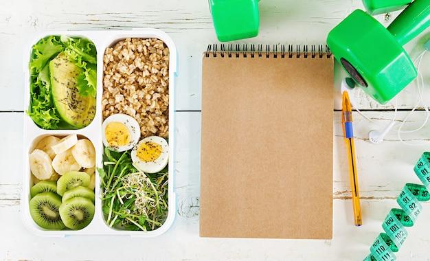 Boîte à lunch avec des œufs à la coque, des flocons d'avoine, des avocats, des micro-verts et des fruits. nourriture saine de remise en forme. à emporter. boîte à déjeuner. vue de dessus Photo Premium
