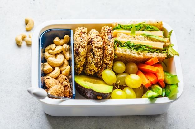 Boîte à lunch saine école avec sandwich, biscuits, fruits et avocat sur fond blanc. Photo Premium