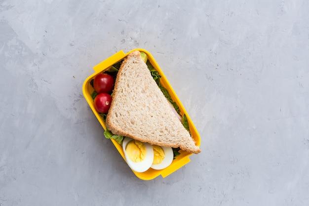 Boîte à lunch avec sandwich et différents produits sur fond gris Photo Premium