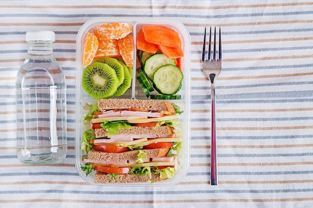 Boîte à lunch avec sandwich, légumes, eau et fruits sur la table. Photo Premium