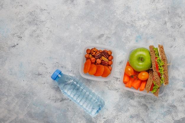 Boîte à lunch avec sandwich, légumes, fruits à blanc. Photo gratuit
