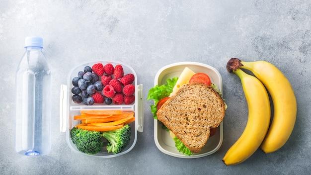 Boîte à lunch scolaire avec sandwich légumes baies banane sur table grise en bonne santé Photo Premium