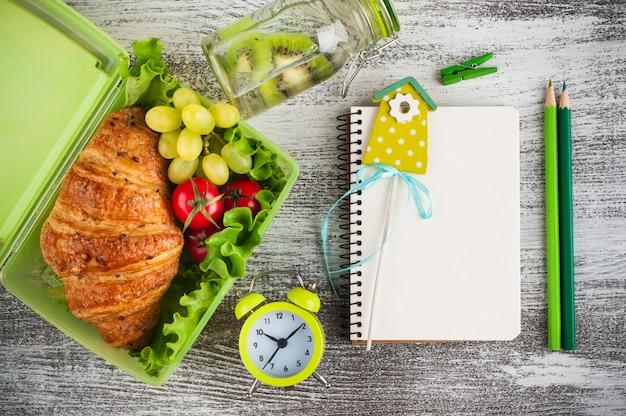 Boîte à lunch verte avec collation et cahier Photo Premium