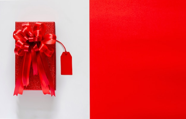 Boîte De Noël Rouge Avec Ruban Arc Rouge Et étiquette De Prix Sur Blanc Et Rouge. Photo Premium