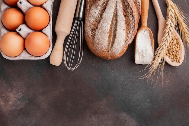 Boîte à œufs avec fouet et pain cuit Photo gratuit