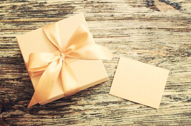 Boîte de papier cadeau artisanal avec ruban arc et étiquette vierge. Photo Premium