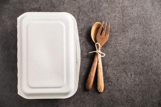 Boîte de papier à emporter avec cuillère et fourchette en bois sur fond de marbre ancien Photo Premium