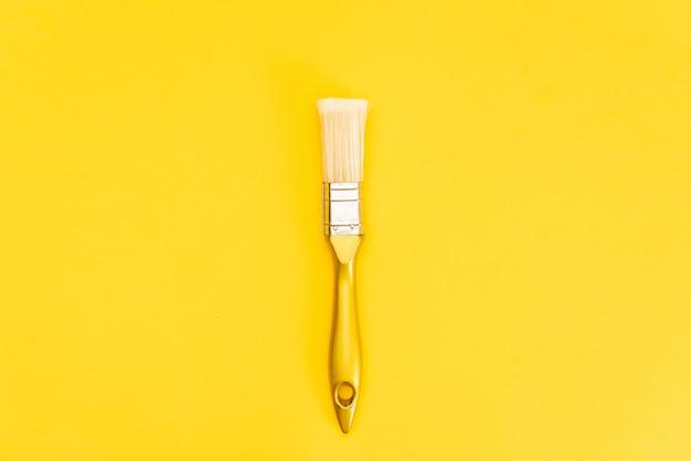 Boîte de peinture blanche avec vue de dessus de pinceau sur fond jaune. Photo Premium