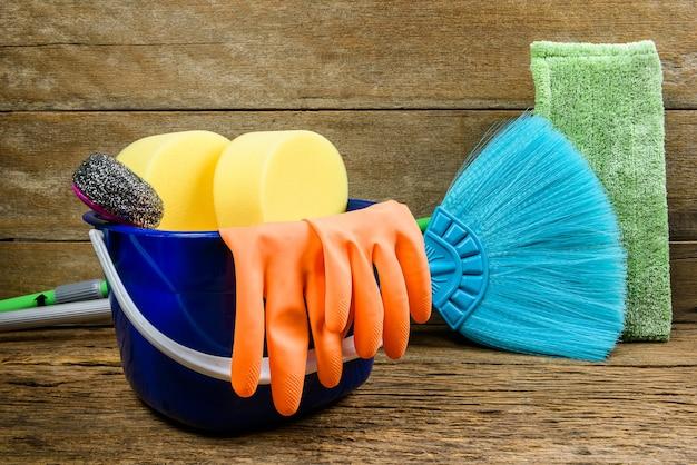 Boîte pleine de produits de nettoyage, vadrouille, balai et gants sur fond de plancher en bois Photo Premium