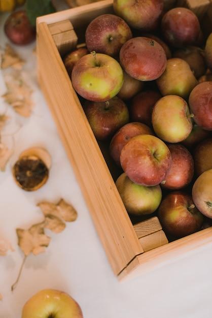 Une Boîte De Pommes Sucrées Rustiques Sur Une Table à La Maison. Automne Nature Morte. Photo Premium