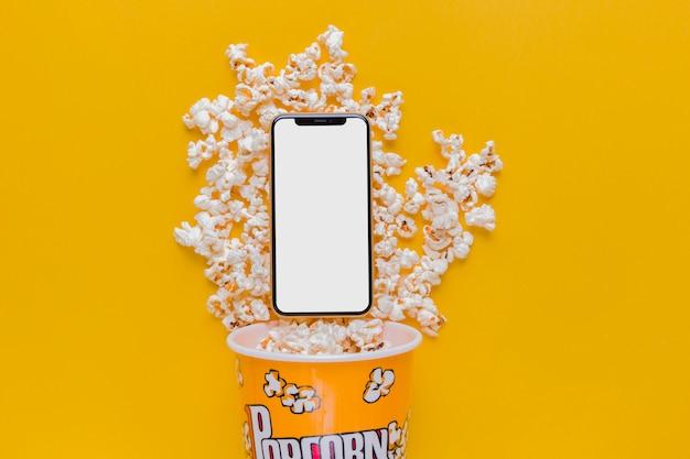 Boîte à pop-corn avec téléphone portable Photo gratuit