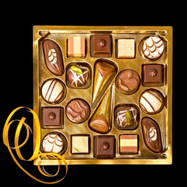 Boîte de pralines au chocolat isolées sur fond noir Photo Premium