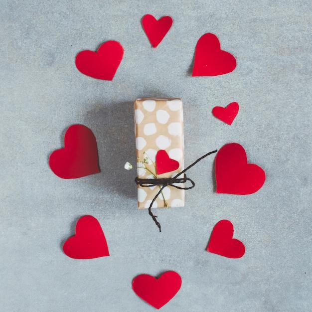 Boîte présente entre un ensemble de coeurs en papier Photo gratuit