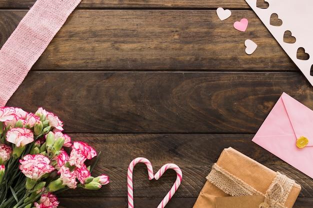 Boîte présente près de fleurs, enveloppe et cannes de bonbon Photo gratuit