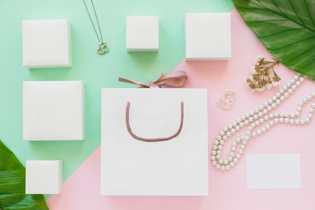 Boîtes à bijoux blancs et sac à provisions sur fond de papier de couleur Photo gratuit