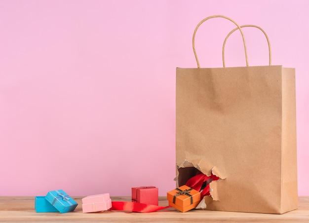 Des boîtes à cadeaux colorées tombent du sac en papier Photo Premium
