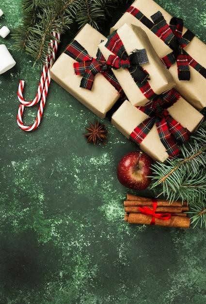 Boîtes avec des cadeaux pour noël et divers attributs de vacances sur une surface verte Photo Premium