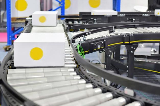 Boîtes en carton sur le concept de système de transport belt.parcels convoyeur Photo Premium