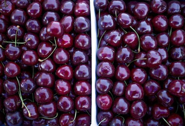 Boites de cerises rouges fraîches, comptoir du vendeur de fruits et légumes, marché fermier Photo Premium