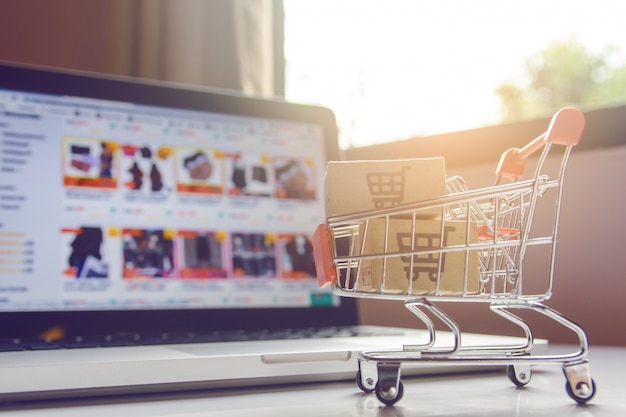 Boîtes De Colis Ou De Papier Avec Le Logo D'un Panier D'achat Dans Un Chariot Sur Un Clavier D'ordinateur Portable. Photo Premium