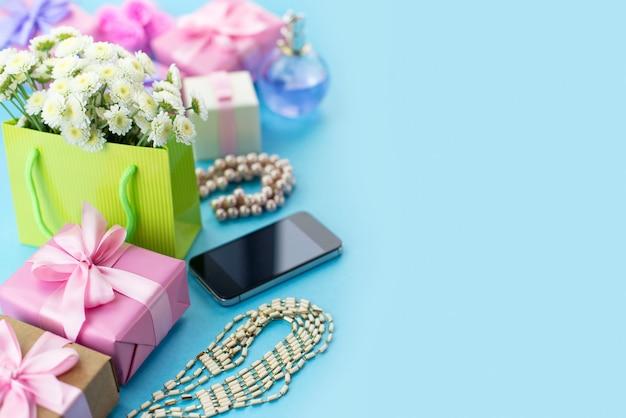 Boîtes de composition décorative avec des bijoux de cadeaux fleurs femmes shopping vacances fond bleu Photo Premium
