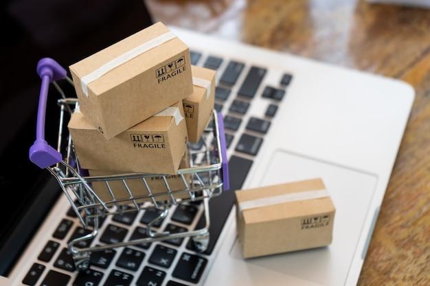 Boîtes de papier dans un chariot sur un ordinateur portable, concept de magasinage en ligne facile Photo Premium