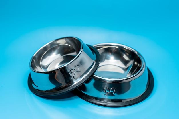 Bol en acier inoxydable sur fond bleu. concept de fournitures pour animaux de compagnie Photo Premium