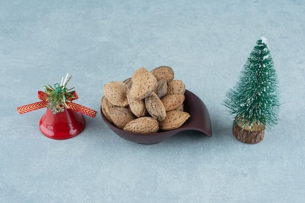 Bol D'amandes Décortiquées Et Décorations De Noël Sur Marbre. Photo gratuit