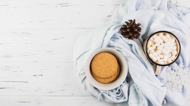 Bol avec des biscuits près de la tasse avec des guimauves et accroc sur l'écharpe Photo gratuit