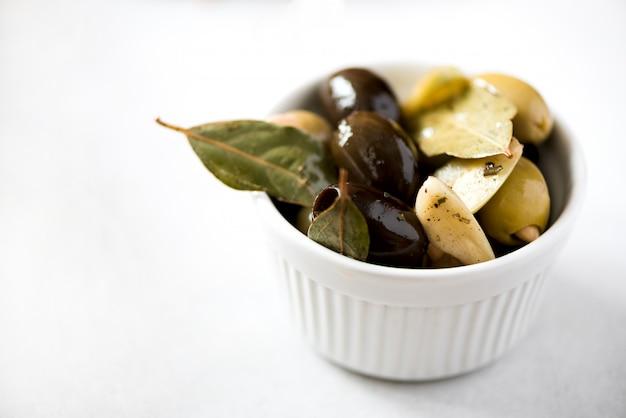 Bol blanc avec olives fraîches noires et vertes, ail, feuilles de laurier sur fond gris. Photo Premium