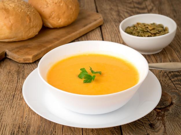 Bol blanc de soupe à la citrouille, garnie de persil sur fond en bois, vue de côté. Photo Premium