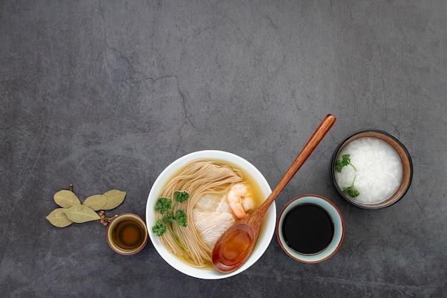 Bol blanc avec soupe de nouilles sur fond gris Photo gratuit