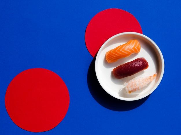 Bol blanc avec sushi sur fond bleu et rouge Photo gratuit