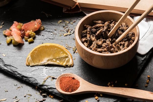 Bol en bois avec insectes sur ardoise Photo gratuit