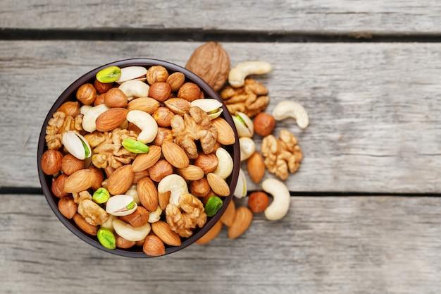 Bol en bois avec des noix mélangées sur un gris en bois. noix, pistaches, amandes, noisettes et noix de cajou, noix. Photo Premium