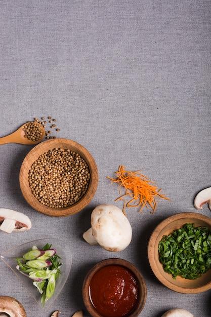Bol en bois d'oignon de printemps; graines de coriandre; sauce; champignons et carottes râpées sur nappe en lin gris Photo gratuit