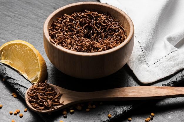 Bol en bois rempli de délicieux insectes Photo gratuit