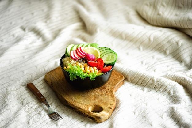 Bol de bouddha avec avocat, quinoa, concombre, radis, salade, citron, tomates cerises, pois chiches, graines de chia sur textile Photo Premium