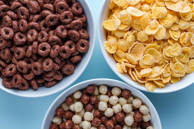 Bol à céréales avec des boules de chocolat, des anneaux et des flocons de maïs jaunes pour le petit déjeuner sec sur une surface bleue Photo Premium