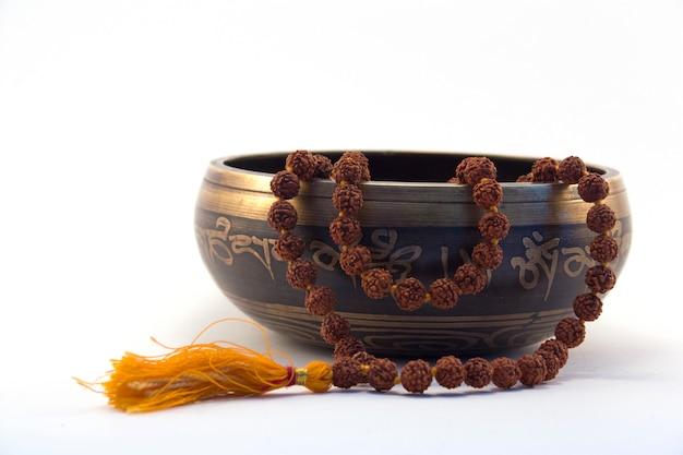 Bol chantant tibétain avec mantra gravé et vue de côté de rudraksa sur blanc Photo Premium