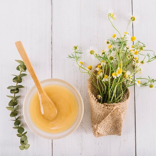 Bol de citron et de belles fleurs de camomille sur fond en bois Photo gratuit