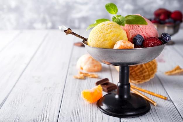 Bol de crème glacée avec trois différentes cuillères de jaune, rouge et cornet de gaufres Photo Premium