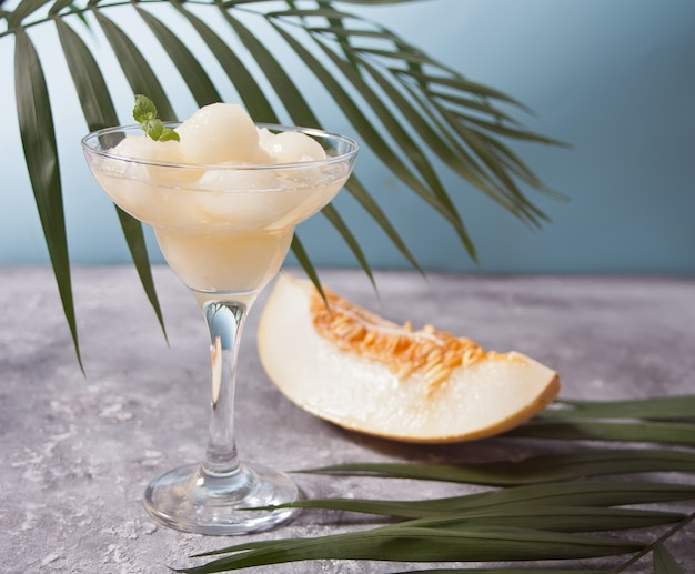 Bol à dessert en verre avec des boules de melon sur la table. Photo Premium