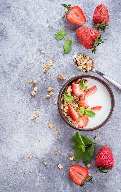 Bol avec du yaourt, granola de muesli et fraises sur fond de table en béton gris Photo Premium