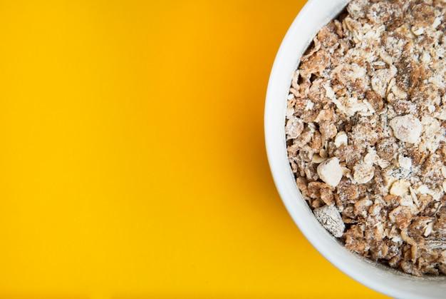 Bol de flocons de farine d'avoine, fond jaune. Photo Premium