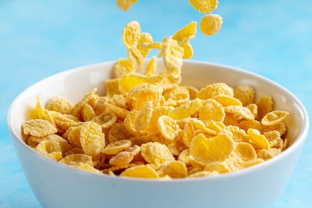 Bol de flocons de maïs givré jaune pour un petit déjeuner sec aux céréales Photo Premium